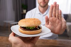 Man Refusing Burger Offered By Person. Close-up Of A Man`s Hand Refusing Burger Offered By Person royalty free stock photo