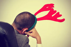 Man with a reindeer antlers headband in his office chair, with a Royalty Free Stock Image