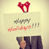 Man with a reindeer antlers headband and a signboard with the te Royalty Free Stock Images
