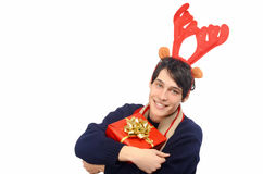 Man with reindeer horns, holding a Christmas gift smiling. Stock Image
