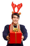 Man with reindeer horns, offering you a Christmas gift smiling. Stock Image