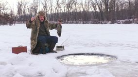 Man rejoices caught fish. Man rejoices caught fish in the winter of the hole stock video