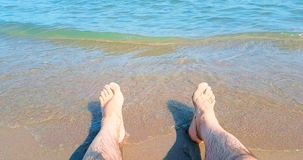 Man in relax stay with  his feet on tropical caribbean beach sea with gold sand, holiday, relax and travel. Concept stock video