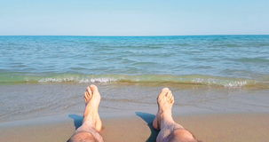 Man in relax stay with his feet on tropical caribbean beach sea with gold sand, holiday, relax and travel stock footage