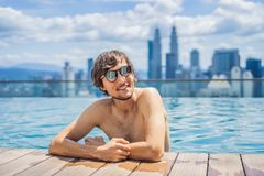 Man relax in swimming pool in sunrise, on rooftop in the city. Rich people.  royalty free stock photo