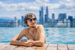 Man relax in swimming pool in sunrise, on rooftop in the city. Rich people.  royalty free stock photos