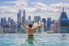 Man relax in swimming pool in sunrise, on rooftop in the city. Rich people.  royalty free stock image