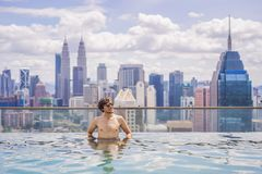 Man relax in swimming pool in sunrise, on rooftop in the city. Rich people.  royalty free stock images