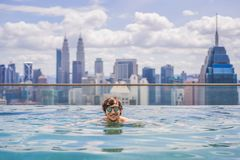 Man relax in swimming pool in sunrise, on rooftop in the city. Rich people.  stock photography