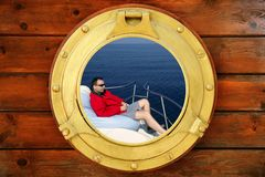 Man relaxed on bean bag. Over blue sea, view from boat round window royalty free stock photos
