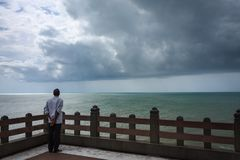 A man relaxedly staring at the vast ocean, Kanyakumari. A man in a relaxed posture, with his back towards the camera is watching the vast ocean and rainy clouds Royalty Free Stock Image