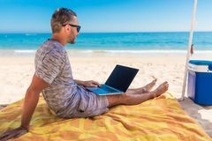 Young man relaxes on the beach under umbrella with laptop surf in internet. The man relaxes on the beach under umbrella with laptop surf in internet royalty free stock photo