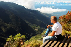 Man relaxes on the edge of the cliff . Plateau ` End of the World ` , Sri Lanka Stock Photos