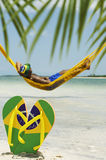 Man Relaxes in Hammock on Brazilian Beach. Man relaxes in hammock over the sea leaving his Brazil flag flip flops in the sand Royalty Free Stock Photo