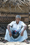 A man relaxes in the shade of a fishing hut on Arugam Bay beach in Sri Lanka. Royalty Free Stock Photos