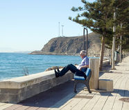 A man relaxing. In sunbeams on the bank at seaside, looking into blue waters Stock Images