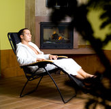 Man relaxing. Photo of man relaxing next to fireplace royalty free stock photos