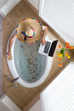 Man relaxing in a bath in a Mexican sombrero Stock Image