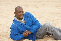 Man Relaxing On Beach In Autumn Clothing Stock Image
