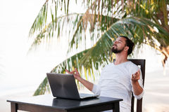 Man relaxing on the beach and doing yoga with laptop, freelancer workplace, dream job Stock Images