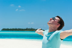 Man relaxing at beach enjoying summer freedom with open arms Stock Images