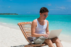 Man relaxing at the beach with laptop. Maldives island, ocean view stock image