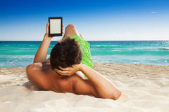 Man relaxing on beach reading e-book Stock Photography