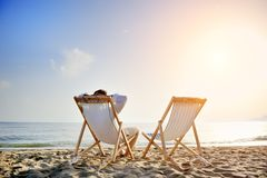 Man relaxing on the beach sitting on deck chair. Man on the beach relaxing on deck chair waiting for his girlfriend royalty free stock image
