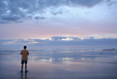 Man relaxing on the beach at sunrise. Stock Photos