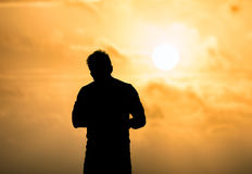 Man relaxing on the beach at sunset, silhouette view. Relax and Royalty Free Stock Photography