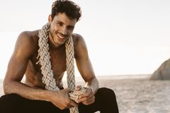 Man relaxing at the beach after workout. Bare chested man relaxing after workout at a beach with a battle rope in his neck. Smiling man taking rest on the beach stock photo