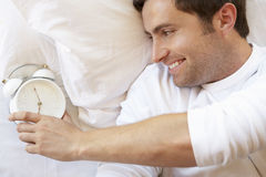 Man Relaxing In Bed With Alarm Clock Royalty Free Stock Photography