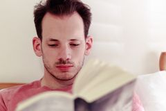 Man relaxing in bed reading book at home stock image