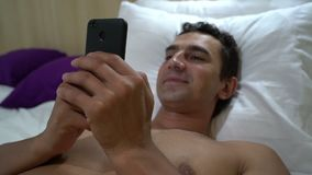 Man relaxing on the bed and reading on smartphone, close up, steadycam shot, leisure activity. Man relaxing on the bed and texting messages on smartphone, close stock video footage