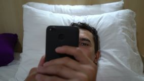 Man relaxing on the bed and reading on smartphone, close up, steadycam shot, leisure activity, tracking shot, cell phone. Man relaxing on the bed and texting stock footage