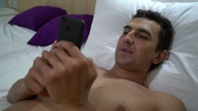 Man relaxing on the bed and reading on smartphone, close up, steadycam shot, leisure activity. Man relaxing on the bed and texting messages on smartphone, close stock video