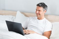 Man relaxing on bed using laptop Royalty Free Stock Photos