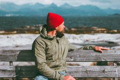 Man relaxing on bench enjoying sea and mountains landscape Norway vacations Traveling Lifestyle concept. Traveler sitting alone we. Aring fashion red hat Stock Photos