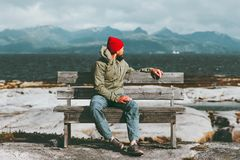 Man relaxing on bench enjoying sea and mountains landscape Travel Lifestyle concept scandinavian. Vacations stock photos