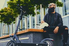 A man relaxing on a bench after riding by electric scooter. Stylish bearded male in sunglasses relaxing on a bench after riding by electric scooter in downtown royalty free stock photo