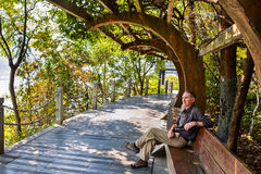Man relaxing on bench under Chinese pergola Royalty Free Stock Photography