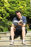 Man relaxing with a book. Outdoor portrait of man reading royalty free stock images