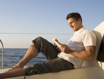 A man relaxing with a book on a boat Stock Photo