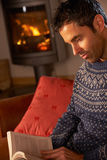 Man Relaxing With Book By Cosy Log Fire. Middle Aged Man Relaxing With Book By Cosy Log Fire Stock Photo
