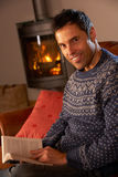 Man Relaxing With Book By Cosy Log Fire Royalty Free Stock Photos