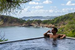 Peaceful tropical getaway. Man relaxing in a  calm pool with an amazing view of the pacific ocean Royalty Free Stock Photography