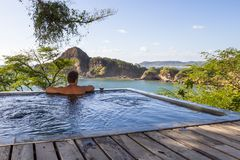 Peaceful tropical getaway. Man relaxing in a  calm pool with an amazing view of the pacific ocean Stock Image