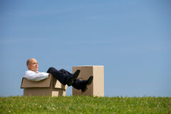 Man relaxing in cardboard box at park Royalty Free Stock Photo