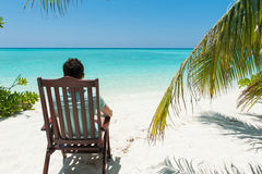 Man relaxing on chair, near palm trees, Maldives stock photos