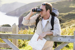 Man relaxing on cliff side path holding map Royalty Free Stock Photos